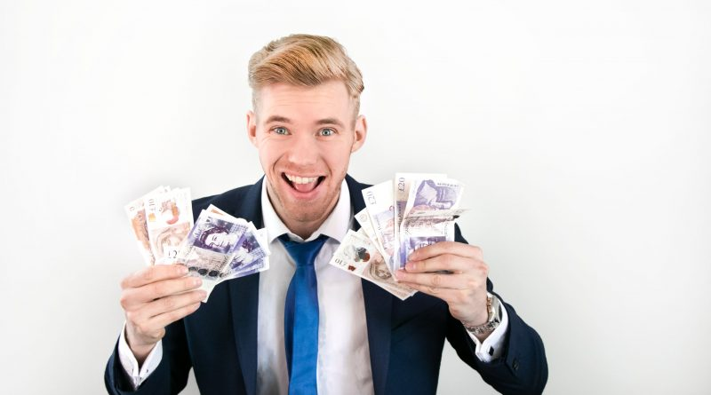 Happy man in suit holding wads of money of pound sterling banknotes in his hands